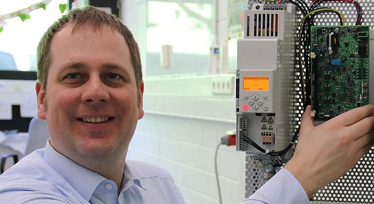 Hochschule OWL/Katharina Thehos | Johann Austermann zeigt die Entwicklung: Die Schaltung auf der grünen Leiterplatte speist die Bremsenergie ins Stromnetz.
