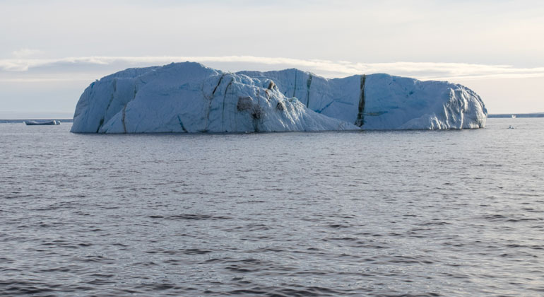 awi.de | Thomas Ronge | An iceberg with enclosed bands of stones and sediments.