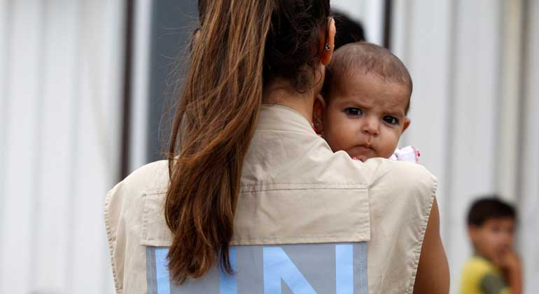 UNHCR/S. Malkawi | UNHCR-Mitarbeiterin kümmert sich um das Baby syrischer Flüchtlinge, während sich die Eltern registrieren lassen - Al Beereh/Libanon.