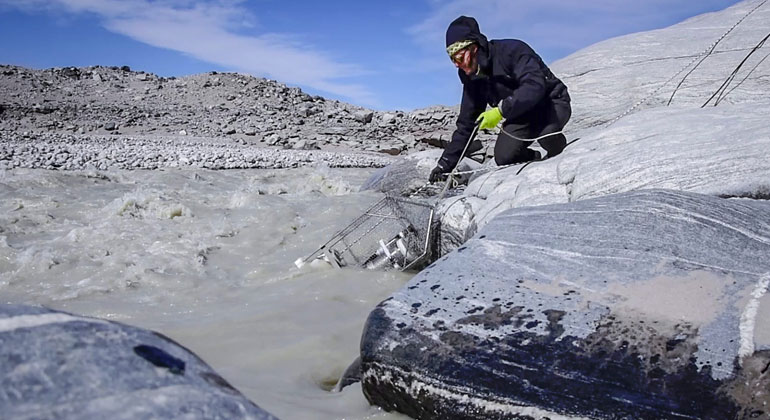 University of Bristol | Marie Bulinova | Guillaume Lamarche-Gagnon sampling some water with a syringe into a vial for later methane analysis, with the Glacier visible in the background.