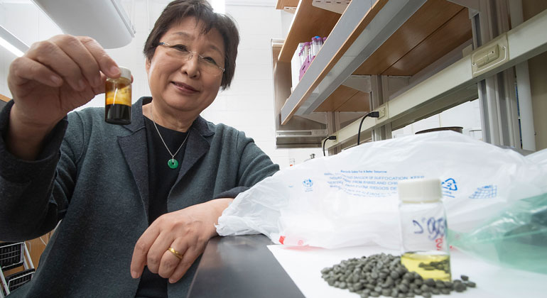 Purdue Research Foundation image/Vincent Walter | A chemical conversion process developed at Purdue University allows researchers to turn recycled shopping bags into pellets into oil as shown in the bottle being held by Linda Wang, the Maxine Spencer Nichols Professor in the Davidson School of Chemical Engineering. Using distillation, that oil is separated into a gasoline-like fuel in the bottle in the counter and a diesel-like fuel not shown.