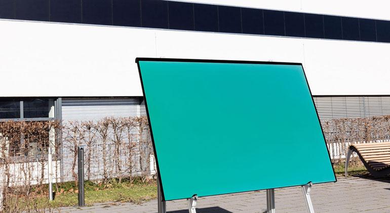 Fraunhofer ISE / Michael Eckmann | In die Fassade eines Institutsgebäudes sind 1mx1m große monokristalline IBC-Solarmodule mit Anti-Blend-Struktur und 210 Wp Leistung integriert. Würde man diese in grün – wie das Modul im Vordergrund – herstellen, hätten sie 195 Wp, also 93% der Leistung des schwarzen Moduls. Im Vordergrund der Prototyp eines farbigen Moduls für die Integration in die Fassade eines neuen Laborgebäudes des Fraunhofer ISE.