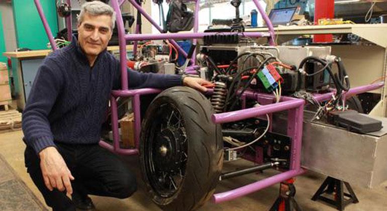 uwaterloo.ca | Amir Khajepour vor einem Prototyp eines dreirädrigen Fahrzeugs, bei dem neue, von den Waterloo Engineering-Forschern entwickelte Radeinheiten verwendet werden.