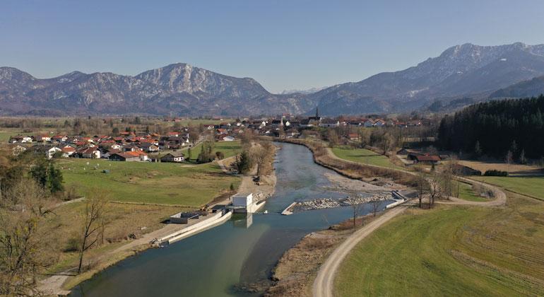TUM | Frank Becht | Weltweit erstes Schachtkraftwerk in der Loisach bei Großweil. Die Turbinen und Generatoren befinden sich in zwei Schächten, die vor der Rampe in das Flussbett gebaut wurden. Am Ufer steht ein Transformatorhäuschen. An beiden Uferbereichen befinden sich Fischtreppen. Das Schachtkraftwerk wurde an der Technischen Universität München (TUM) entwickelt, die Pilotanlage wird von der Wasserkraft Großweil GmbH betrieben.