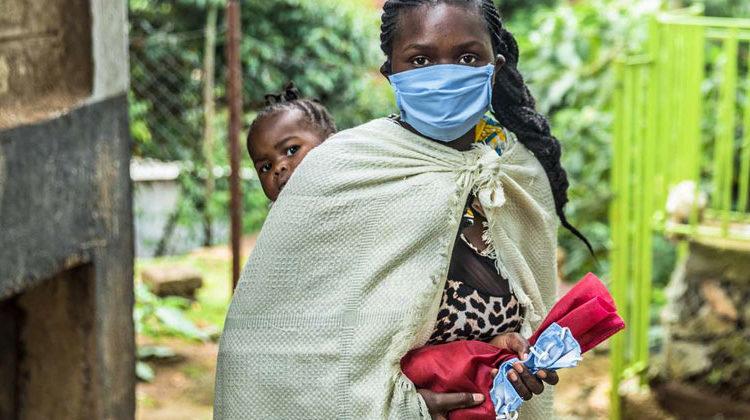 Welthungerhilfe | Natalia Jidovanu | Nahrungsmittelverteilung in Zeiten von Corona: Die Kenianerin Madeline Shimuli, 22 Jahre alt, holt zusammen mit ihrer zweijährigen Tochter - kontaktlos - Lebensmittel von der Welthungerhilfe im St. Charles Lwanga Centre in Kibera, Nairobi ab.